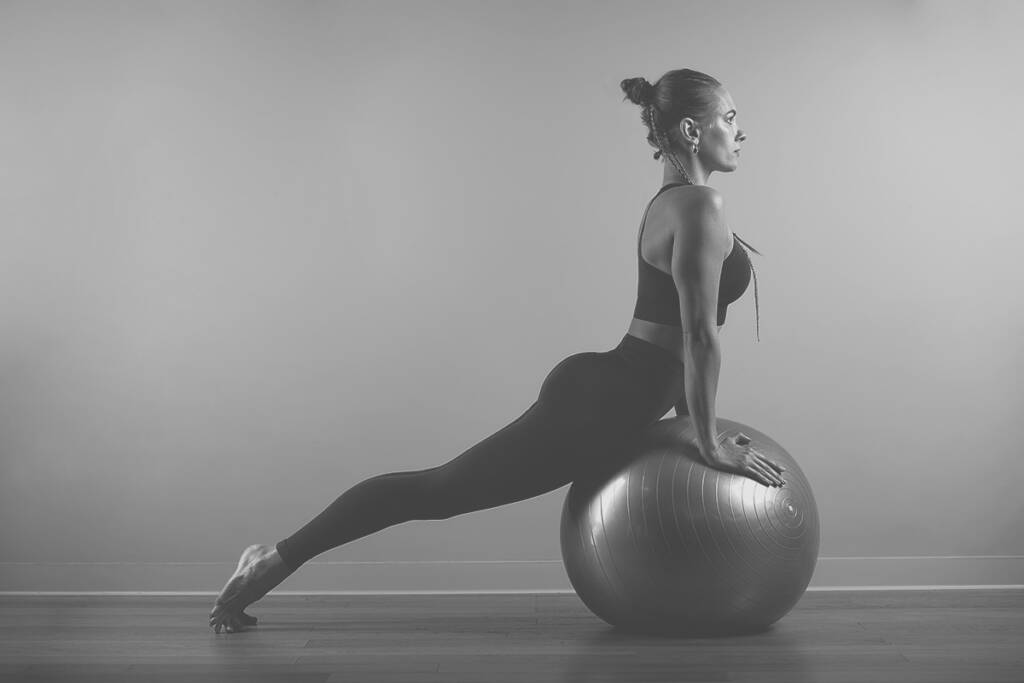 Young, Beautiful, Athletic Girl Doing Exercises On Fitball In The Gym On A Gray Background. Sporting Slavic Girl In A Blue, Green Suit. Copy Space, Gray Background, Sport Banner For Advertising.